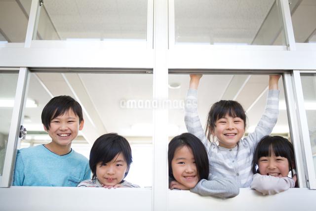 窓から顔を出す小学生の写真素材 [FYI04263966]