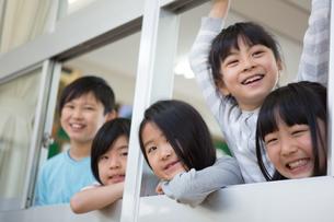 窓から顔を出す小学生の写真素材 [FYI04263968]