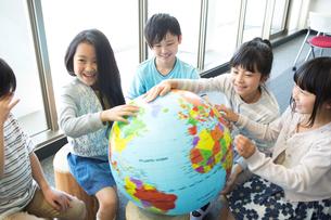 地球儀を持った小学生の写真素材 [FYI04264205]