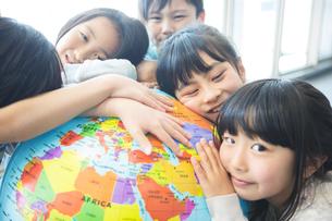 地球儀を持った小学生の写真素材 [FYI04264209]