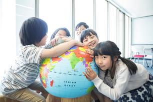 地球儀を持った小学生の写真素材 [FYI04264211]