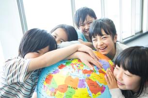 地球儀を持った小学生の写真素材 [FYI04264212]