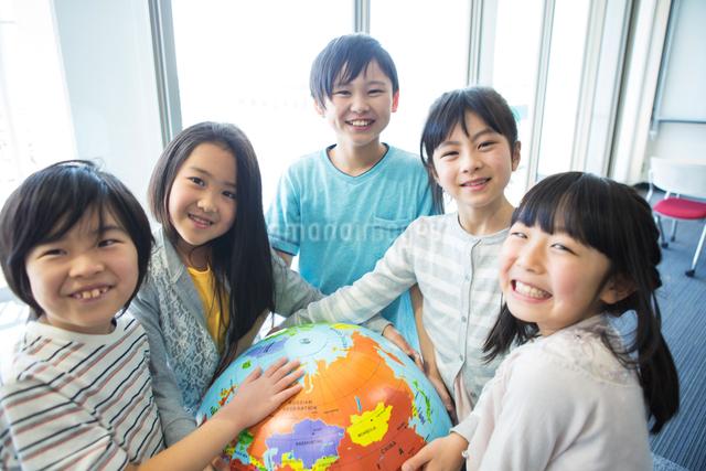 地球儀を持った小学生の写真素材 [FYI04264213]