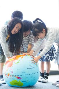 地球儀を持った小学生の写真素材 [FYI04264217]