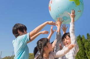 地球儀を持ち上げる小学生の写真素材 [FYI04264409]