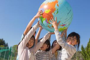 地球儀を持ち上げる小学生の写真素材 [FYI04264410]