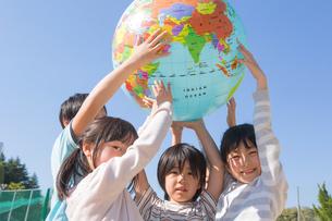 地球儀を持ち上げる小学生の写真素材 [FYI04264413]