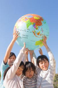 地球儀を持ち上げる小学生の写真素材 [FYI04264415]