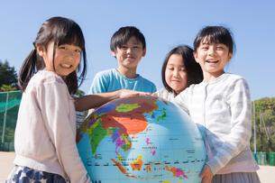 地球儀を持つ小学生の写真素材 [FYI04264422]