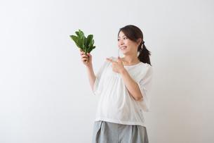 ほうれん草を持つ妊婦さんの写真素材 [FYI04264860]