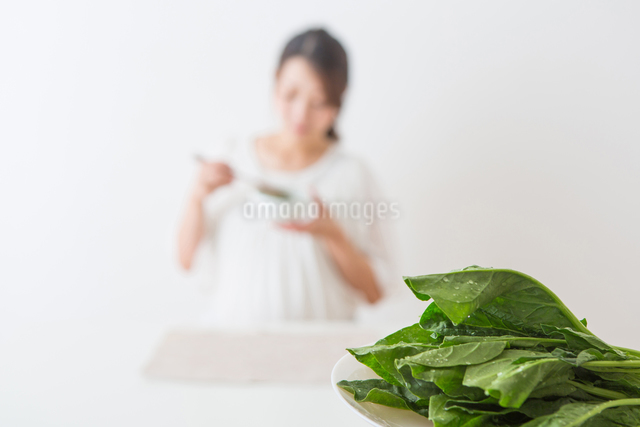 ほうれん草を食べる妊婦さんの写真素材 [FYI04264882]