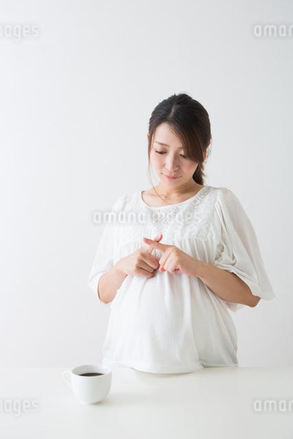 コーヒーを見る妊婦さんの写真素材 [FYI04264901]