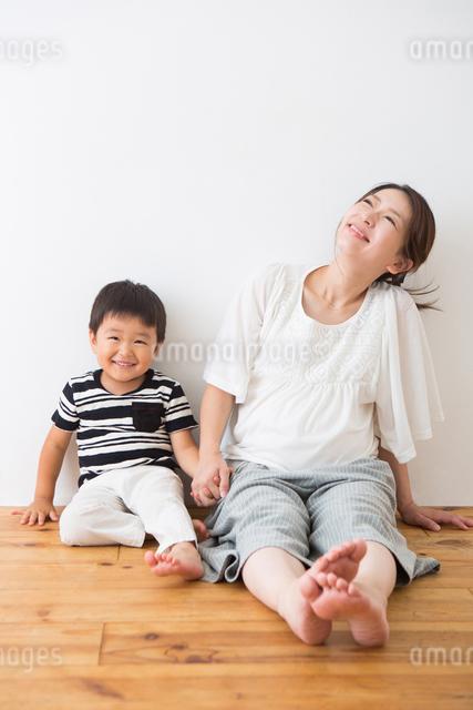 フローリングに座る男の子と妊婦さんの写真素材 [FYI04264931]