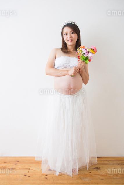 花束を持つドレスを着た妊婦さんの写真素材 [FYI04265009]
