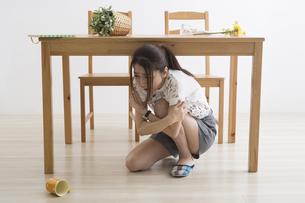 地震でテーブル下に避難する女性の写真素材 [FYI04265087]