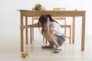 地震でテーブル下に避難する女性の写真素材 [FYI04265088]