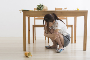 地震でテーブル下に避難する女性の写真素材 [FYI04265089]