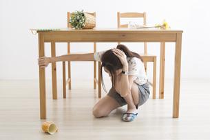 地震でテーブル下に避難する女性の写真素材 [FYI04265090]