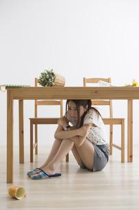 地震でテーブル下に避難する女性の写真素材 [FYI04265091]