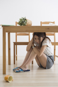 地震でテーブル下に避難する女性の写真素材 [FYI04265092]