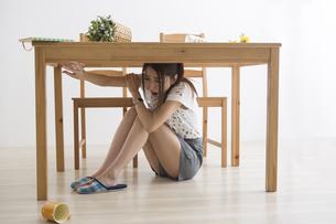 地震でテーブル下に避難する女性の写真素材 [FYI04265093]