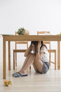 地震でテーブル下に避難する女性の写真素材 [FYI04265094]
