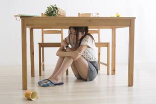 地震でテーブル下に避難する女性の写真素材 [FYI04265095]