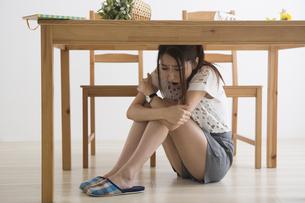 地震でテーブル下に避難する女性の写真素材 [FYI04265096]