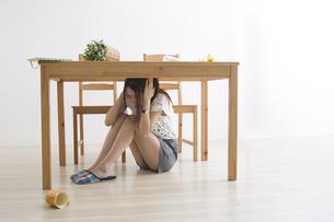 地震でテーブル下に避難する女性の写真素材 [FYI04265097]