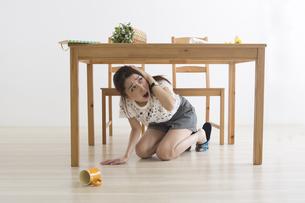 地震でテーブル下に避難する女性の写真素材 [FYI04265098]