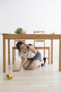 地震でテーブル下に避難する女性の写真素材 [FYI04265099]