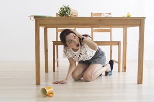 地震でテーブル下に避難する女性の写真素材 [FYI04265100]