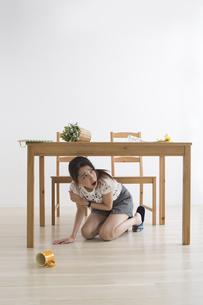 地震でテーブル下に避難する女性の写真素材 [FYI04265101]