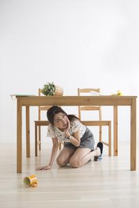 地震でテーブル下に避難する女性の写真素材 [FYI04265102]
