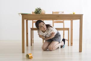 地震でテーブル下に避難する女性の写真素材 [FYI04265103]
