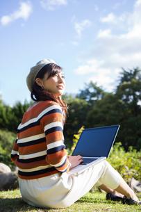 公園でノートパソコンを使う女性の写真素材 [FYI04265371]