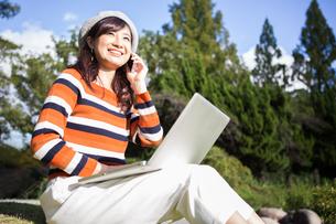 公園でノートパソコンを使う女性の写真素材 [FYI04265374]