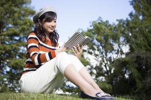 公園で読書を楽しむ女性の写真素材 [FYI04265385]