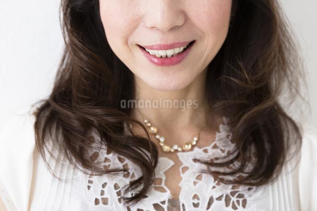 白壁にもたれるミドル女性の写真素材 [FYI04265524]