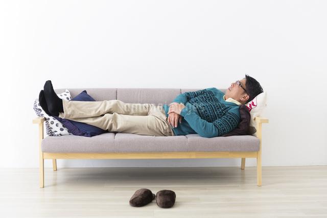 ソファでうたた寝するミドル男性の写真素材 [FYI04265601]