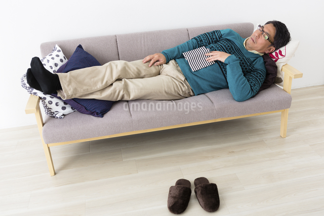 ソファでうたた寝するミドル男性の写真素材 [FYI04265602]