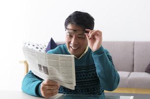 新聞を読むミドル男性の写真素材 [FYI04265608]