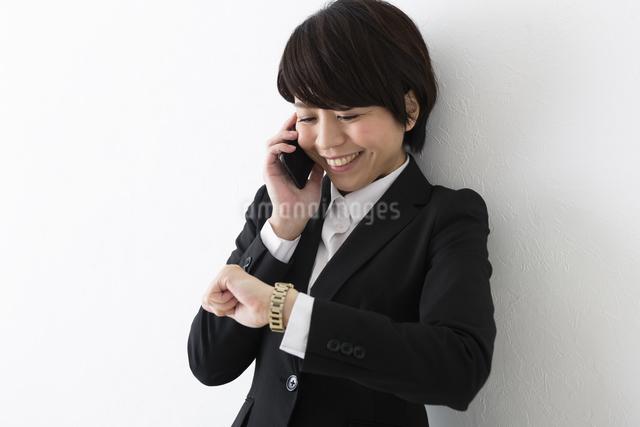 時計を見ながら電話するビジネスウーマンの写真素材 [FYI04265675]
