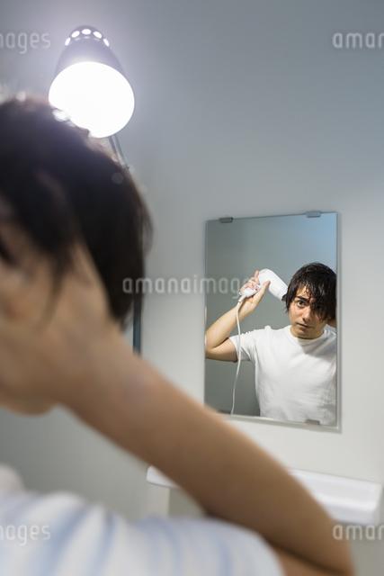 ドライヤーで髪を乾かす男性の写真素材 [FYI04265965]