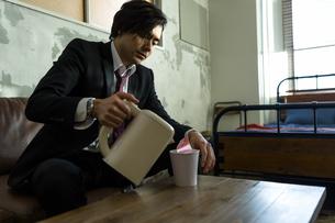 カップ麺にお湯を注ぐ男性の写真素材 [FYI04266198]