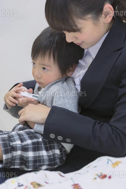 体温計で熱を測る子供の写真素材 [FYI04266620]
