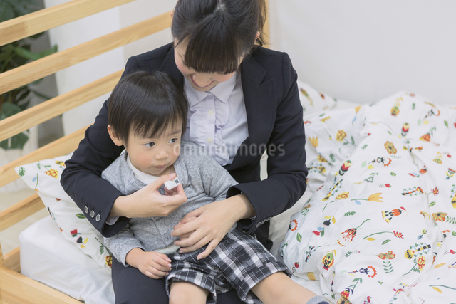 体温計で熱を測る子供の写真素材 [FYI04266621]