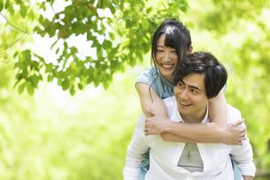 おんぶをして歩くカップルの写真素材 [FYI04267315]
