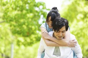 おんぶをして歩くカップルの写真素材 [FYI04267325]