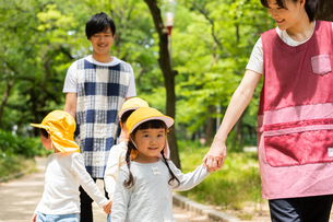 公園を散歩する保育士と園児の写真素材 [FYI04267704]